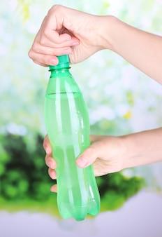Bottiglia con apertura a mano con acqua dolce sulla superficie naturale