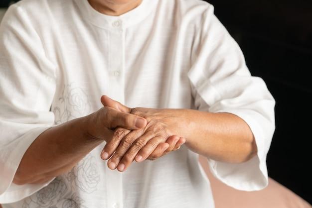 Dolore alla mano della donna anziana, problema sanitario del concetto senior