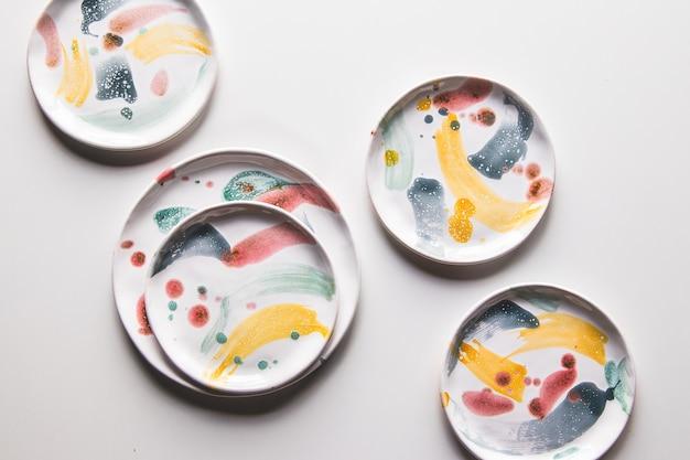 Piatti in ceramica dipinta a mano. collezione di ceramica colorata su sfondo bianco