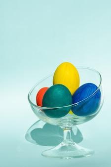 Uova di pasqua colorate dipinte a mano in un vaso di vetro trasparente contro una superficie azzurra, cornice verticale, spazio copia, primo piano. felice pasqua concetto.