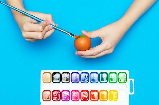 Uova di pasqua dipinte a mano prima di pasqua. preparazione per la pasqua, su sfondo blu. vernice multicolore, copia spazio.