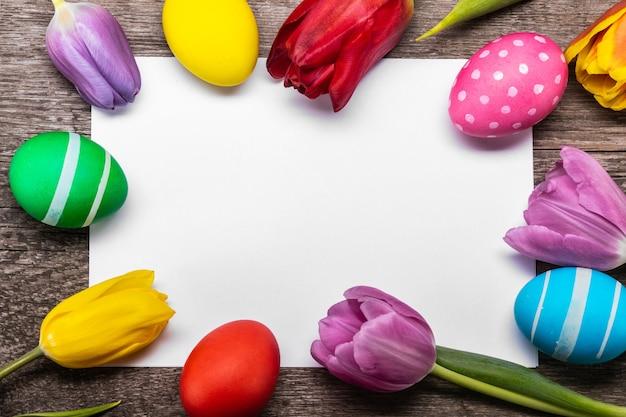 Uova di pasqua dipinte a mano con i tulipani sulla cartolina d'auguri in bianco sopra lo spazio della copia del fondo di legno per testo