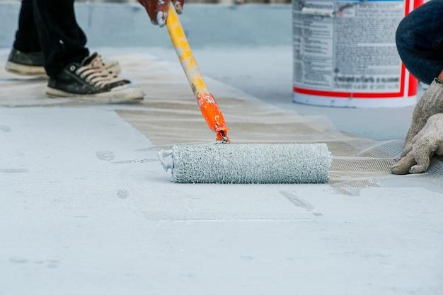Pavimento grigio dipinto a mano con rulli di vernice per rete di rinforzo impermeabile