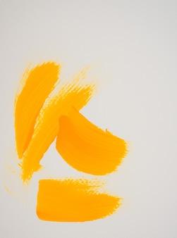 Pennellate acriliche gialle dipinte a mano su sfondo bianco texture fluida su tela