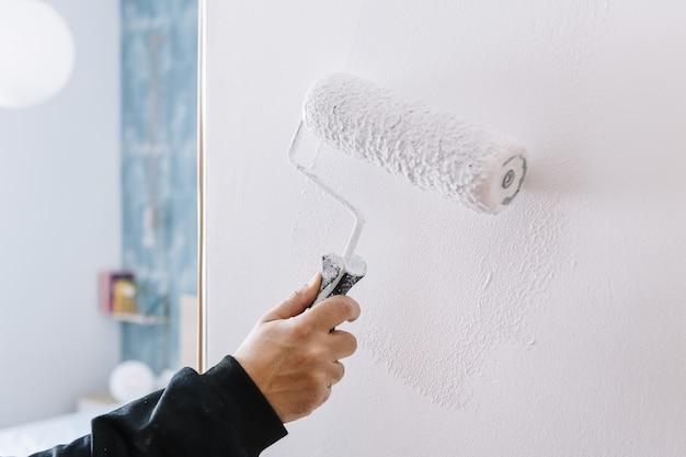 Dipinto a mano un muro in bianco con un rullo