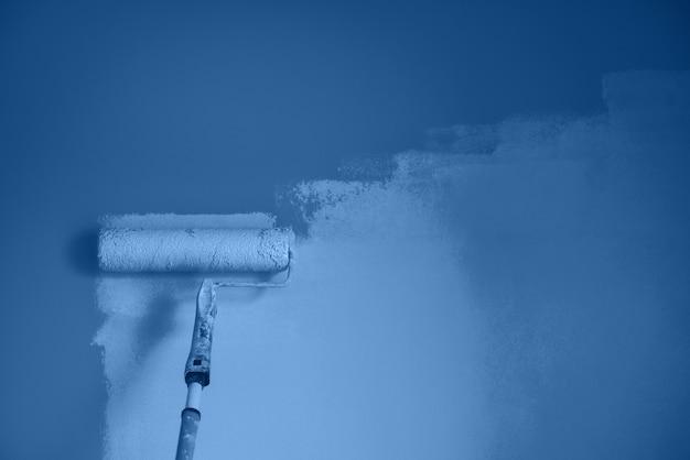 Muro dipinto a mano con rullo di vernice in colore bianco e nero. ristrutturazione, riparazione, costruzione e concetto domestici dell'appartamento. colore blu e calmo alla moda. strumenti per dipingere pareti.