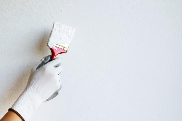Dipinto a mano un muro bianco con un pennello