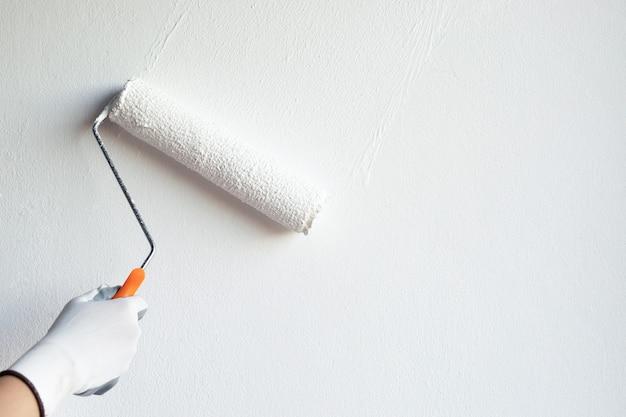 Dipinto a mano un muro bianco con un rullo di vernice