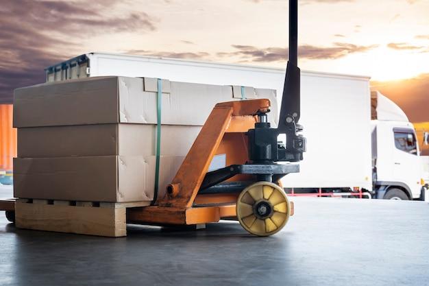 Transpallet manuale con carico di pacchi con carico su camion per la spedizione del carico logistica per il trasporto merci