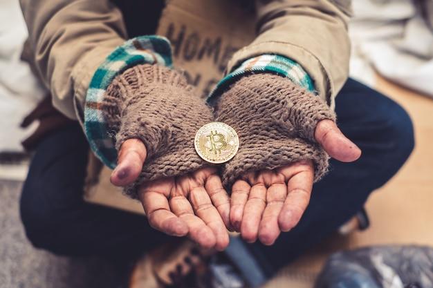 Mano palmo senzatetto sporco con ricevere in donazione un bitcoin dorato