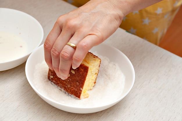 Mano che passa in cocco grattugiato tradizionale dolce brasiliano chiamato in portoghese brasiliano: bolo gelado.