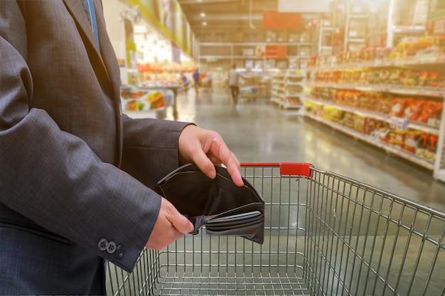 La mano della gente mostra il portafoglio vuoto nel supermercato per lo shopping, il concetto di economia
