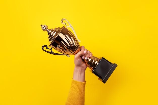 Mano della persona con una coppa sportiva su sfondo giallo