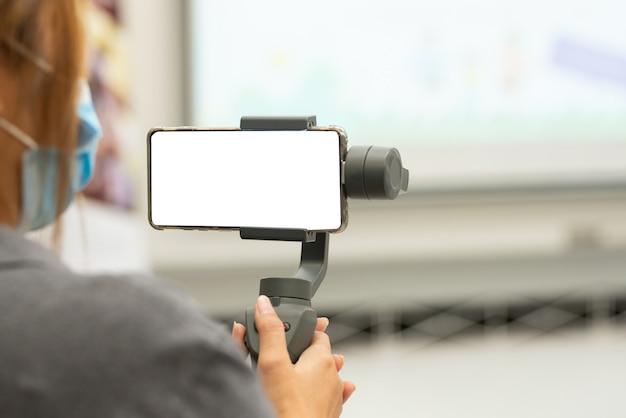 La gente della mano pf tiene lo stabilizzatore per il telefono cellulare, smartphone nella sala riunioni