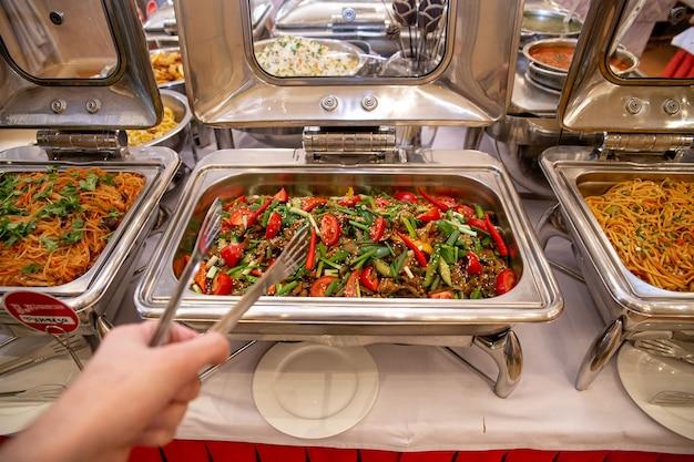 La mano raccoglie carne e verdure durante un pranzo di lavoro in un bar.