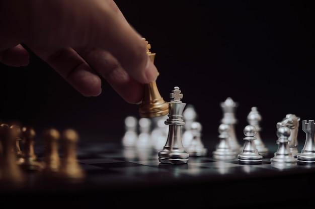Mano che gioca scacchi d'oro e d'argento