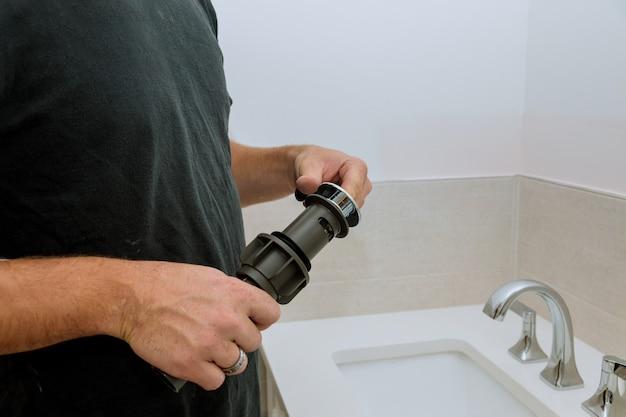 L'idraulico a mano tiene il gruppo di scarico della fogna vicino al rubinetto