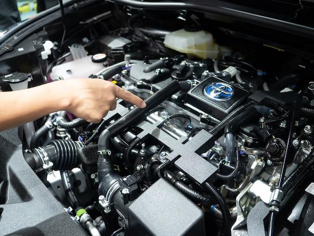 La mano punta il dito sui dettagli del motore della nuova auto pulita e lucida