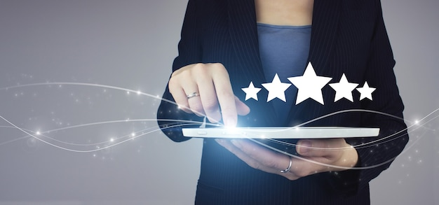 Mano che indica il simbolo a cinque stelle per aumentare la valutazione dell'azienda. compressa bianca in mano di donna d'affari con ologramma digitale cinque stelle 5 segno di valutazione su sfondo grigio.