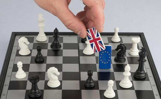 La politica della mano alza la figura con la bandiera della gran bretagna gioco politico e strategia di scacchi brexit
