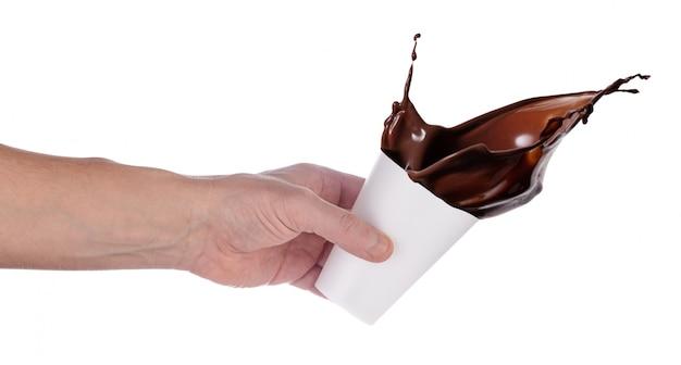 Mano che versa cioccolata calda dal bicchiere di plastica bianca