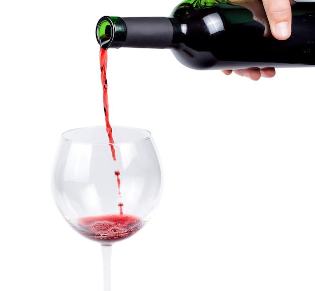 Mano che versa vino rosso in un bicchiere da vino da una bottiglia di vino senza etichetta isolata su bianco