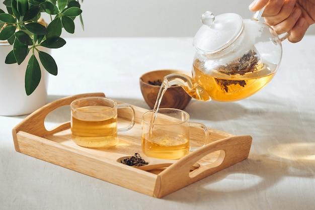 Un tè di versamento della mano dalla teiera di vetro sul vassoio di legno del servizio