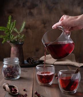 Una mano versa il tè alla rosa rossa da una teiera di vetro in tazze trasparenti su un tavolo di legno marrone. vista frontale