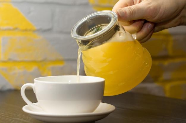 La mano versa il tè giallo allo zenzero con il ramo di limone e rosmarino dalla teiera trasparente nella tazza bianca sul tavolo di legno scuro