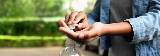 Premere a mano il gel alcolico dalla bottiglia e l'applicazione di disinfettante per le mani rendono il virus della pulizia covid 19