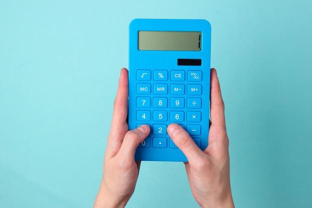 La mano preme i pulsanti calcolatrice blu su blu.