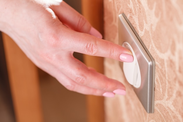 La mano preme l'interruttore della luce sulla parete