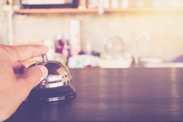 Mano premendo un servizio di chiamata campanello di servizio sul caffè caffè o ristorante contatore da vicino