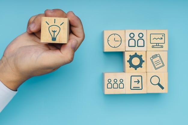 Mano di un uomo d'affari professionista che tiene in mano un blocco di legno idea per fare un passo verso il successo, l'innovazione e il concetto di creatività