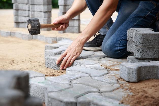 La mano dell'operaio della finitrice professionale depone le pietre per lastricati a strati per il concetto di percorso, lavoro e industria.