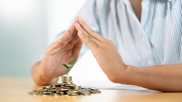 La mano protegge la copertura protegge un giovane albero che cresce sulle monete del mucchio per il risparmio dall'investimento di rischio e dal concetto di assicurazione.