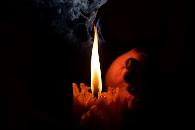 Mano che protegge la luce della candela dal vento nell'oscurità