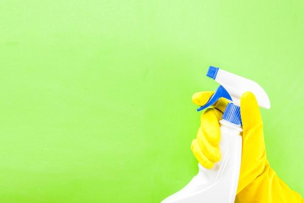 Mano in guanti protettivi con spray. spazio verde della copia del fondo