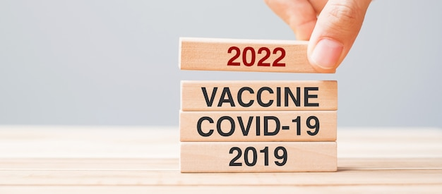 Tirando a mano il blocco 2022 su vaccine, covid-19 e 2019 edificio in legno sullo sfondo del tavolo. economia di crisi, vaccinazione, immunizzazione e pandemia di coronavirus ( covid-19 )