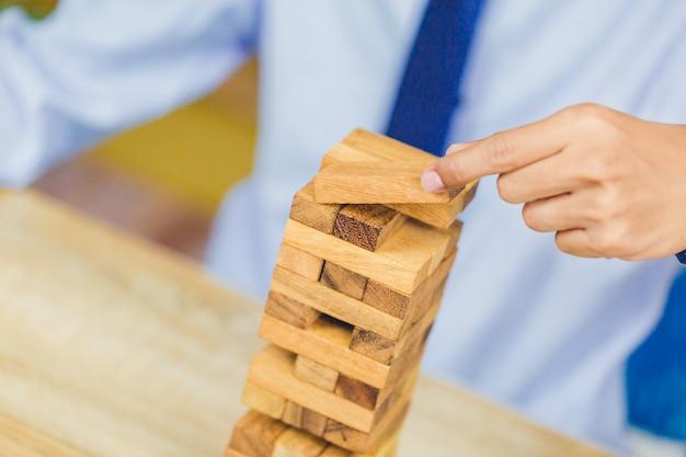 Mano estraendo o posizionando il blocco di legno sulla torre, piano e strategia nel mondo degli affari