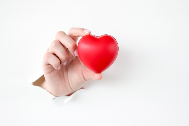 Mano che tira fuori il cuore rosso del giocattolo da carta strappata