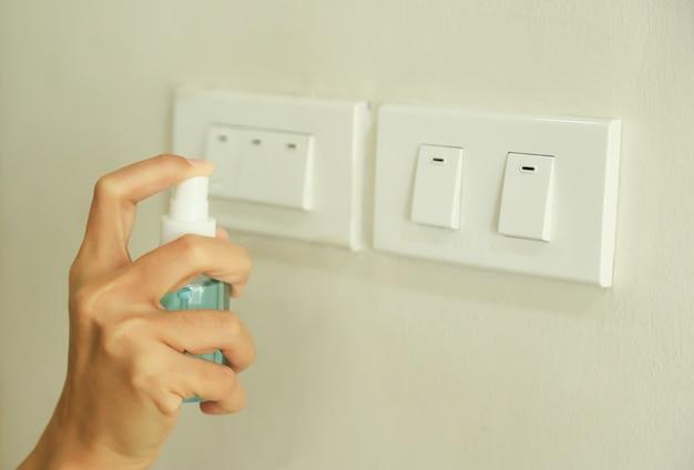 Spray manuale con gel per alcool per la pulizia dello scambiatore di luce prima di utilizzare la stanza durante il giorno dalla fuga da virus vocid o corona. la gente si prende cura di vivere la vita dal concetto di virus corona.
