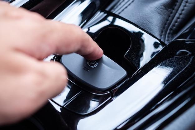Spingere a mano sul pulsante del freno a mano elettronico in auto moderne di lusso