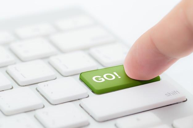 Mano spingendo andare pulsante verde sulla tastiera