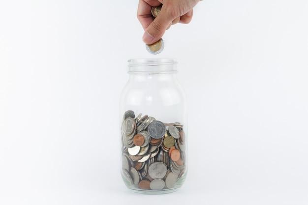 La mano ha messo la moneta nella bottiglia di vetro. finanza, concetto di economia. concetto di risparmio di denaro.