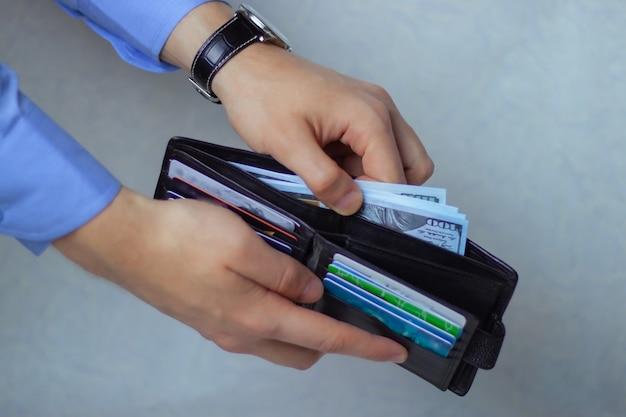 La mano mette i soldi in una scatola per immagazzinare l'accumulo.