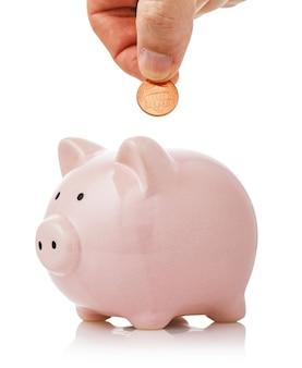 La mano mette un centesimo nel concetto di salvadanaio sul tema del risparmio