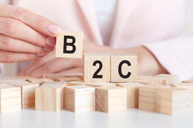 Mano mette un cubo di legno con la lettera b2c. abbreviazione b2c per business to consumer