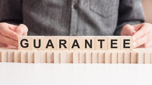 La mano mette un cubo di legno con la lettera di garanzia. la parola è scritta su cubi di legno in piedi sulla superficie bianca del tavolo.
