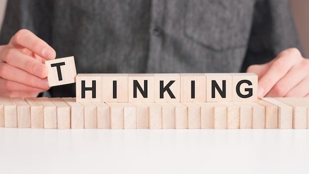 La mano mette un cubo di legno con la lettera t dalla parola pensiero